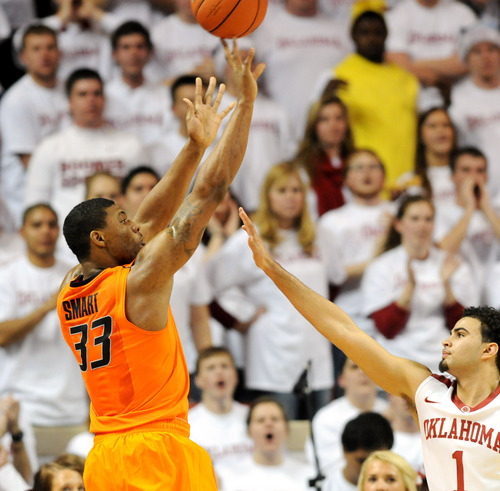 Oklahoma State guard Marcus Smart (33) takes a shot over Oklahoma guard Marcus Smart  (1) during the second half of an NCAA college basketball game in Norman, Okla., Monday, Jan. 27, 2014. Smart scored 22 points in the 76-88 loss to  rival Oklahoma. (AP Photo/Brody Schmidt)
