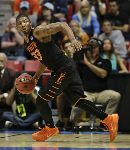 Oklahoma State guard Marcus Smart grabs a loose ball during the first half in a second-round game against Gonzaga in the NCAA college basketball tournament Friday, March 21, 2014, in San Diego. (AP Photo/Gregory Bull)