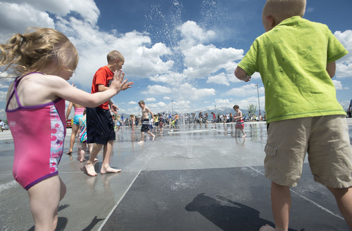 Steve Griffin  |  The Salt Lake Tribune Children play in the water area during the grand opening of the Sierra Newbold Playground in West Jordan, Utah Friday, May 30, 2014. The playground is named after the 6-year-old girl who was abducted from her home on June 26, 2012, and killed. The new playground is part of the Ron Wood Park which is named after West Jordan Officer Ron Wood who was shot and killed Nov. 18, 2002, by a 17-year-old suspect wanted in connection with a string of burglaries. When all phases are complete, the park will total about 64 acres.