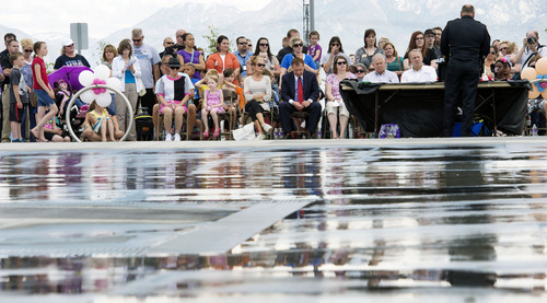 Steve Griffin  |  The Salt Lake Tribune   People are reflected on the cement of the fountain play area during the grand opening of the Sierra Newbold Playground in West Jordan, Utah Friday, May 30, 2014. The playground is named after the 6-year-old girl who was abducted from her home on June 26, 2012, and killed. The new playground is part of the Ron Wood Park, which is named after a West Jordan police officer who was shot and killed Nov. 18, 2002, by a 17-year-old suspect wanted in connection with a string of burglaries. When all phases are complete, the park will total about 64 acres.