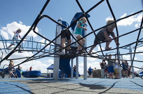 Steve Griffin  |  The Salt Lake Tribune   People play in the playground during the grand opening of the Sierra Newbold Playground in West Jordan, Utah Friday, May 30, 2014. The playground is named after the 6-year-old girl who was abducted from her home on June 26, 2012, and killed. The new playground is part of the Ron Wood Park, named after a West Jordan officer who was shot and killed Nov. 18, 2002, by a 17-year-old suspect wanted in connection with a string of burglaries. When all phases are complete, the park will total about 64 acres.