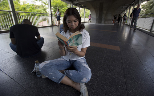 Kasama Na Nagara, who works in the financial sector, reads a book along an elevated walkway during a protest in Bangkok, Thailand, Saturday, May 31, 2014. In junta-ruled Thailand where the army recently took power in a coup, the simple act of reading in public has become an act of resistance. (AP Photo/Sakchai Lalit)