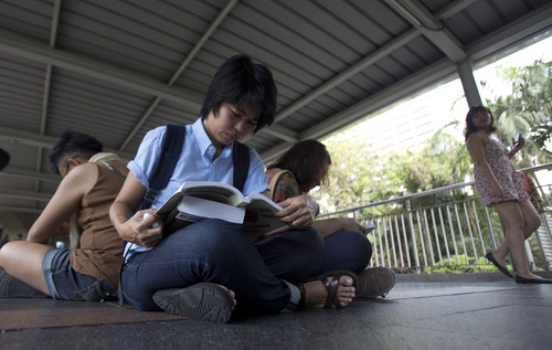 Mook, front left, reads a book along an elevated walkway during a protest in Bangkok, Thailand, Saturday, May 31, 2014. In junta-ruled Thailand where the army recently took power in a coup, the simple act of reading in public has become an act of resistance. (AP Photo/Sakchai Lalit)