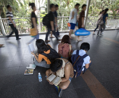 A group of anti-coup protesters read books along an elevated walkway during a protest in Bangkok, Thailand, Saturday, May 31, 2014. In junta-ruled Thailand where the army recently took power in a coup, the simple act of reading in public has become an act of resistance. (AP Photo/Sakchai Lalit)