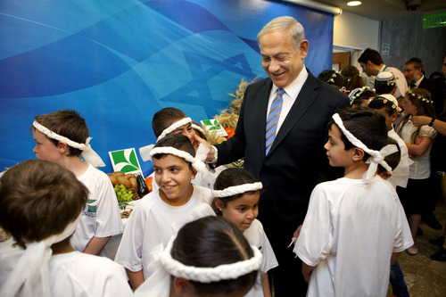 Israeli Prime Minister Benjamin Netanyahu meets Israeli children on the Jewish holiday of Shavout. which marks the harvest of the first fruits of the season, before the cabinet meeting in Jerusalem, Sunday, June 1, 2014. (AP Photo/Dan Balilty, Pool)