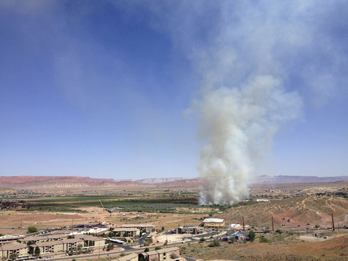 Courtesy Jud Burkett  |  The Spectrum Smoke from a wildfire burning south of the Virgin River and Riverside Drive near the construction site of the new Mall Drive Bridge rises into the air Sunday, June 1, 2014 in St. George.