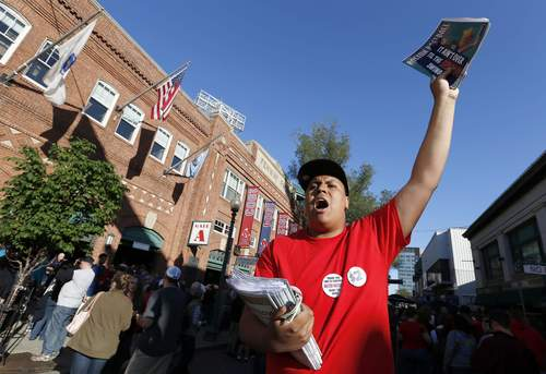 Chris Suazo, of Brookline, Mass., sells programs outside Fenway Park in Boston before a baseball game between the Boston Red Sox and the Tampa Bay Rays, Saturday, May 31, 2014. (AP Photo/Michael Dwyer)