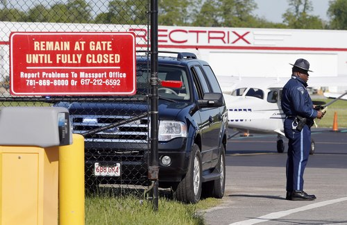 A Massachusetts state police officer stands guard at an entry gate to the tarmac at Hanscom Field in Bedford, Mass., Sunday, June 1, 2014.   A Gulfstream IV crashed as it was leaving Hanscom Field at about 9:40 p.m. Saturday for Atlantic City, New Jersey. There were no survivors. (AP Photo/Michael Dwyer)
