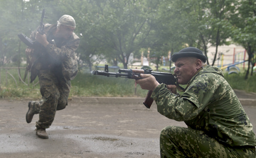 A pro-Russian rebel fires his weapon during clashes with Ukrainian troops on the outskirts of Luhansk, Ukraine, Monday, June 2, 2014. Hundreds of pro-Russia insurgents attacked a border guard base in eastern Ukraine on Monday, with some firing rocket-propelled grenades from the roof of a nearby residential building. At least five rebels were killed when the guards returned fire, a spokesman for the border guard service said.(AP Photo/Vadim Ghirda)