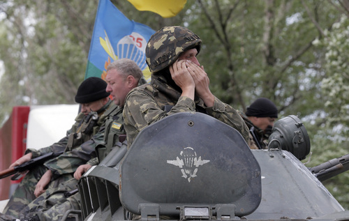 Ukrainian army paratroopers move to position in Slovyansk, Ukraine, Monday, June 2, 2014. Hundreds of armed insurgents attacked a border guards' camp in eastern Ukraine Monday, as rebels nearby promised safety for the officers if they surrendered the base and lay down their arms. (AP Photo/Efrem Lukatsky)