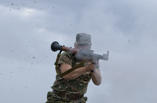 A pro-Russian rebel fires a rocket propelled grenade on the rooftop of an apartment building during clashes with Ukrainian troops on the outskirts of Luhansk, Ukraine, Monday, June 2, 2014. Hundreds of pro-Russia insurgents attacked a border guard base in eastern Ukraine on Monday, with some firing rocket-propelled grenades from the roof of a nearby residential building. At least five rebels were killed when the guards returned fire, a spokesman for the border guard service said.(AP Photo/Vadim Ghirda)