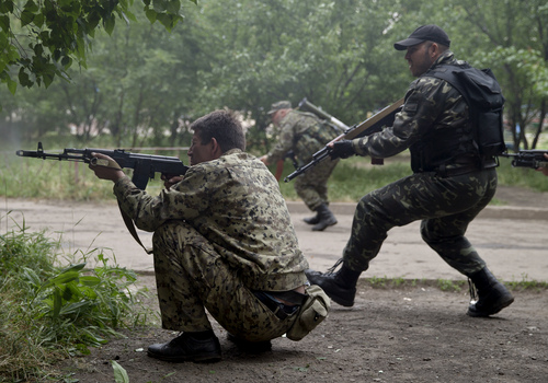 Pro-Russian rebels fire their weapons during clashes during clashes as they attack a border guard base held by Ukrainian troops on the outskirts of Luhansk, eastern Ukraine, Monday, June 2, 2014. Some hundreds of pro-Russia insurgents attacked the base on Monday, with some firing rocket-propelled grenades from the roof of a nearby residential building. At least five rebels were killed when the guards returned fire, a spokesman for the border guard service said. (AP Photo/Vadim Ghirda)
