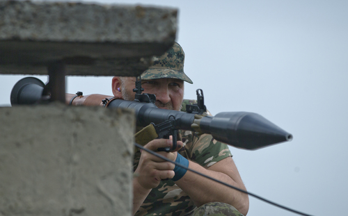A pro-Russian rebel prepares to fire a rocket propelled grenade on the rooftop of an apartment building during clashes during clashes as they attack a border guard base held by Ukrainian troops on the outskirts of Luhansk, eastern Ukraine, Monday, June 2, 2014. Some hundreds of pro-Russia insurgents attacked the base on Monday, with some firing rocket-propelled grenades from the roof of a nearby residential building. At least five rebels were killed when the guards returned fire, a spokesman for the border guard service said. (AP Photo/Vadim Ghirda)