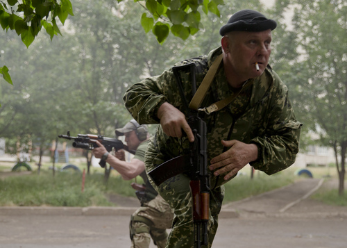 A pro-Russian rebel runs for cover during clashes with Ukrainian troops on the outskirts of Luhansk, Ukraine, Monday, June 2, 2014. Hundreds of pro-Russia insurgents attacked a border guard base in eastern Ukraine on Monday, with some firing rocket-propelled grenades from the roof of a nearby residential building. At least five rebels were killed when the guards returned fire, a spokesman for the border guard service said.(AP Photo/Vadim Ghirda)