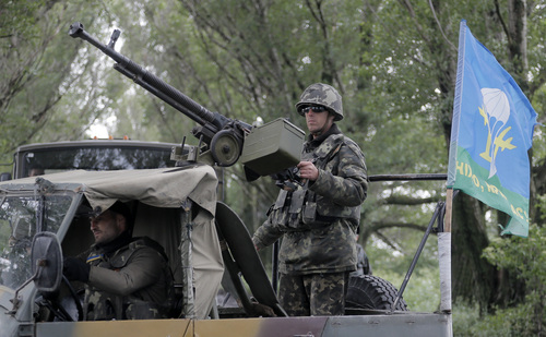 Ukrainian army paratroopers move to a position in Slovyansk, Ukraine, Monday, June 2, 2014. Hundreds of armed insurgents attacked a border guards' camp in eastern Ukraine Monday, as rebels nearby promised safety for the officers if they surrendered the base and lay down their arms. (AP Photo/Efrem Lukatsky)