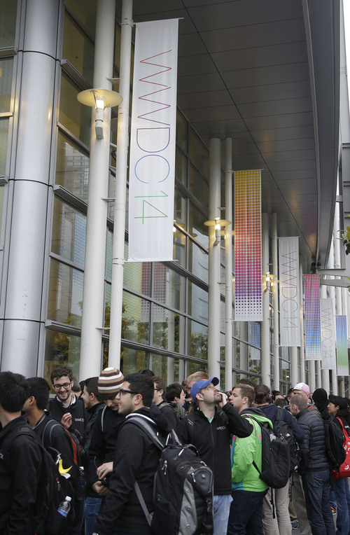 A crowd lines up before the Apple World Wide Developers Conference 2014 at the Moscone Center in San Francisco, Monday, June 2, 2014. This week should provide a better sense of whether Apple is heading down promising new avenues of growth or whether it's still wandering aimlessly around well-trod territory in search of another breakthrough. (AP Photo/Jeff Chiu)