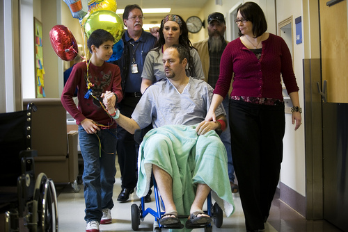Deputy Greg Sherwood, center, is joined by his wife Gina Sherwood, right, son Braxton, left, and other family and friends as he is moved from his hospital room to a recovery ward at Utah Valley Regional Medical Center in Provo Monday, Feb. 10, 2014.   MARK JOHNSTON/Daily Herald