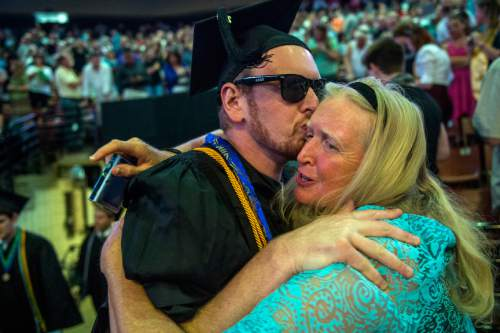 Chris Detrick  |  The Salt Lake Tribune Randall Coates Nigohosian kisses his mom Margo Coates Huddleston before Westminster College's Commencement at the Maverik Center Saturday May 31, 2014. 977 students graduated. Nigohosian graduated with a Bachelors in special education and elementary education.