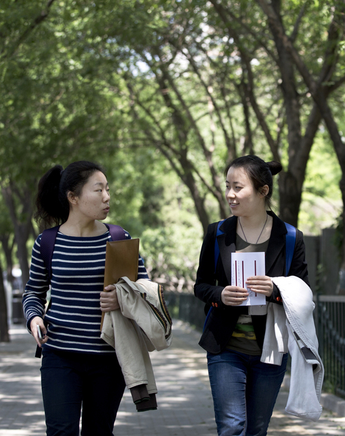 In this May 7, 2014 photo, Wang Jiaying, right, chats with Lu Qiuxuan as they walk outside their university in Beijing, China. A quarter century after the Communist Party's attack on demonstrations centered on Tiananmen Square on June 4, 1989, it is little more than a distant tale to young Chinese. The ruling party prohibits public discussion and 1989 is banned from textbooks and Chinese websites.(AP Photo/Andy Wong)