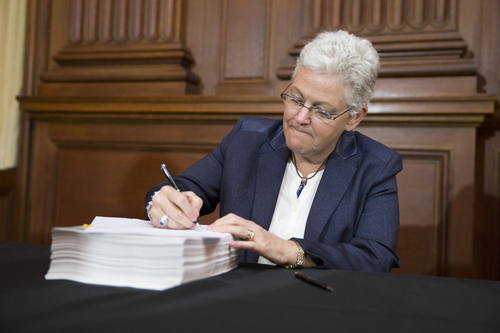 Environmental Protection Agency (EPA) Administrator Gina McCarthy signs new emission guidelines during an announcement of a plan to cut carbon dioxide emissions from power plants by 30 percent by 2030, Monday, June 2, 2014, at EPA headquarters in Washington. In a sweeping initiative to curb pollutants blamed for global warming, the Obama administration unveiled a plan Monday that cuts carbon dioxide emissions from power plants by nearly a third over the next 15 years, but pushes the deadline for some states to comply until long after President Barack Obama leaves office. (AP Photo/ Evan Vucci)
