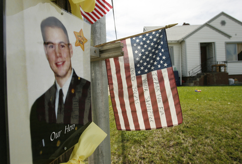 Above, the telephone pole outside the 37th Street home in South Ogden is decorated with Army Staff Sgt. Kurt Curtiss' photo and a flag that another South Ogden resident placed there thanking Curtiss for his service. Army Staff Sgt. Kurt Curtiss was on a recovery mission at a hospital with his unit when he was caught in crossfire and killed, said his sister, Lynn Burr. Curtiss has lived in both Utah and Arizona. He served two tours of duty in Iraq before being transferred to Fort Richardson in Alaska. He was deployed to Afghanistan last year, and had been home for a visit about a month ago. Photo by Leah Hogsten/ The Salt Lake Tribune S. Ogden 8/28/09