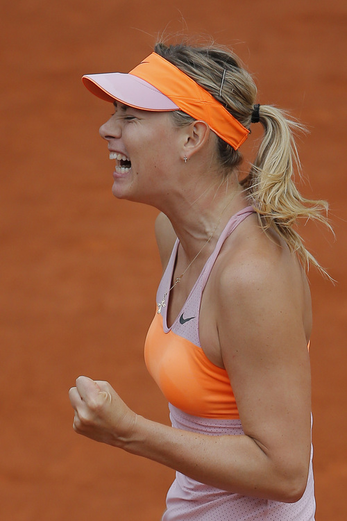 Russia's Maria Sharapova clenches her fist after scoring a point during the quarterfinal match of the French Open tennis tournament against Spain's Garbine Muguruza at the Roland Garros stadium, in Paris, France, Tuesday, June 3, 2014.(AP Photo/Michel Spingler)