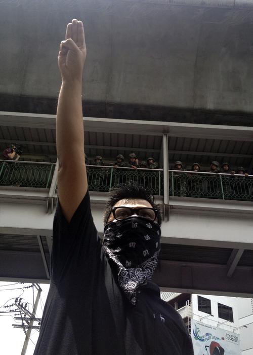 """In this Sunday, June 1, 2014 photo, an anti-coup protester gives a three-finger salute as soldiers keep eyes on him from an elevated walkway near a rally site in central Bangkok, Thailand. Thailand's military rulers say they are monitoring the new form of silent resistance to the coup - borrowed from """"The Hunger Games"""" - and will arrest those in large groups who ignore warnings to lower their arms. The raised arm salute has become an unofficial symbol of opposition to Thailand's May 22 coup, and a creative response to several bans the ruling junta has placed on freedom of expression. Some protesters in Thailand say it represents: liberty, equality, fraternity. (AP Photo/Thanyarat Doksone)"""