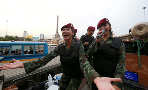 """Thai female soldiers entertain passers by while providing security at the Victory Monument in Bangkok, Thailand Tuesday, June 3, 2014. Thailand's military rulers say they are monitoring a new form of silent resistance to the coup - a three-fingered salute borrowed from """"The Hunger Games"""" - and will arrest those in large groups who ignore warnings to lower their arms. (AP Photo/Wason Wanichakorn)"""