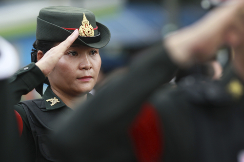 """A Thai soldier salutes while providing security at Victory Monument in Bangkok, Thailand Tuesday, June 3, 2014. Thailand's military rulers say they are monitoring a new form of silent resistance to the coup - a three-fingered salute borrowed from """"The Hunger Games"""" - and will arrest those in large groups who ignore warnings to lower their arms. (AP Photo/Wason Wanichakorn)"""