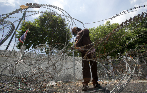 A Thai worker removes barbed wire from the government house in Bangkok, Thailand Tuesday, June 3, 2014. Thailand has been calm since the army overthrew the nation's elected government on May 22, saying it had to restore order after seven months of demonstrations that had triggered sporadic violence and left the country's political rivals in a stalemate.(AP Photo/Sakchai Lalit)