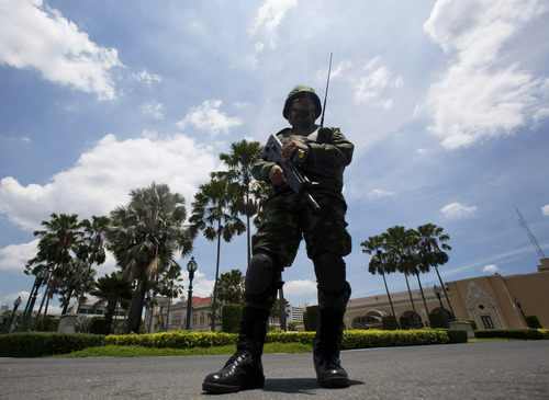 A Thai soldier guards at Government house in Bangkok, Thailand Tuesday, June 3, 2014. Thailand has been calm since the army overthrew the nation's elected government on May 22, saying it had to restore order after seven months of demonstrations that had triggered sporadic violence and left the country's political rivals in a stalemate.(AP Photo/Sakchai Lalit)