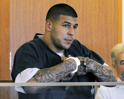FILE - In this June 27, 2013, file photo, former New England Patriots NFL football player Aaron Hernandez stands during a bail hearing in Superior Court in Fall River, Mass. Hernandez is accused of three murders in Massachusetts. Investigators have appealed for information from tattoo artists who inked his right forearm, but won't say which of Hernandez's many tattoos prompted their appeal. (AP Photo/Boston Herald, Ted Fitzgerald, Pool, File)