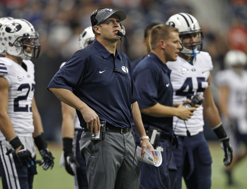 FILE - BYU head coach Bronco Mendenhall, center, stands on the sidelines during the second half of an NCAA college football game against Houston, Saturday, Oct. 19, 2013 in Houston. BYU defeated Houston, 47-46. (AP Photo/Eric Christian Smith)