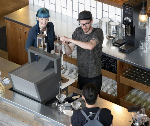 Al Hartmann  |  The Salt Lake Tribune Baristas Lacy Hardwick and Dylan Sands help customers counterside at the newly opened Publik Coffee Roasters at 975 S. West Temple.   The refurbished building used to be a print shop. Beans from around the world are shipped in and roasted in a high-tech computerized roaster. It's a two-story building and one can look down on the main floor from the upper seating area that has Wi-Fi and meeting rooms. The menu is all toast using Utah-made bread with different toppings: from butter and jam to avocado.
