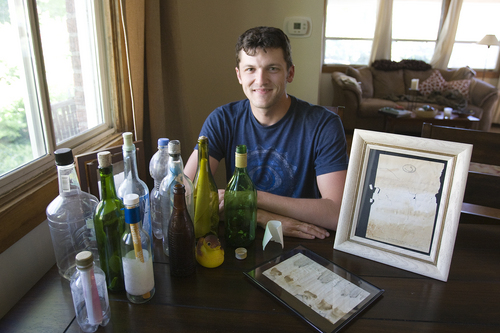 (Melissa Majchrzak  |  Special to the Tribune) Clint Buffington poses with his collection of messages in bottles that he has found in the Caribbean islands over the course of several trips.
