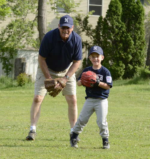 Steve Hauser coaches his grandson, Owen Newcomer, before a Little League game in Williamsport, Pa. , May 28, 2014. He is the son of Dick Hauser who played on one of the original Little League teams in 1939, making him the second and Newcomer the fourth generation to play Little League. (AP Photo/Ralph Wilson)