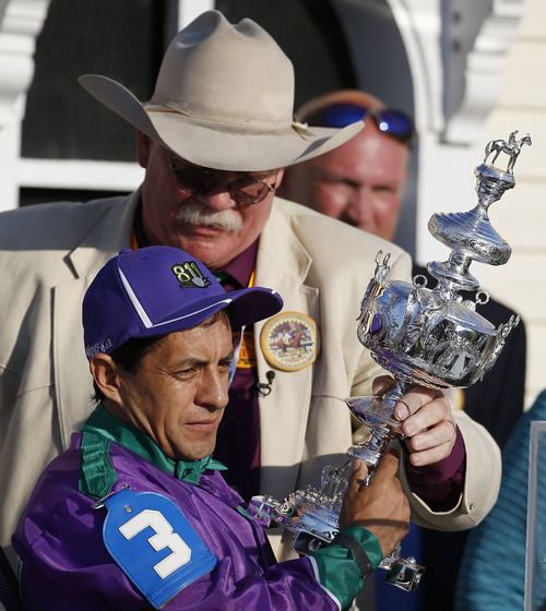California Chrome's co-owner Steve Coburn, top, and jockey Victor Espinoza hold a trophy after winning the 139th Preakness Stakes horse race at Pimlico Race Course, Saturday, May 17, 2014, in Baltimore.  (AP Photo/Matt Slocum)
