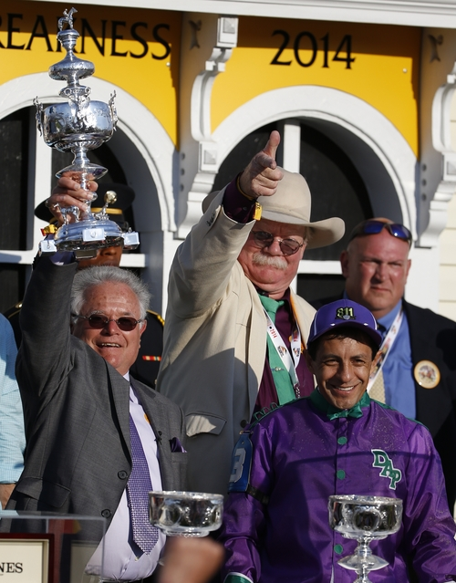 California Chrome's Co-Owner Steve Coburn, center, trainer Art Sherman, left, and jockey Victor Espinoza, bottom right, celebrate in winner's circle after California Chrome won the 139th Preakness Stakes horse race at Pimlico Race Course, Saturday, May 17, 2014, in Baltimore.  (AP Photo/Matt Slocum)