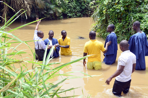 Mike Stack  |  special to The Salt Lake Tribune  Adventist Pastor Richard Daves baptizes new convert in flooding river near Pokause, Ghana.  03/01/2014