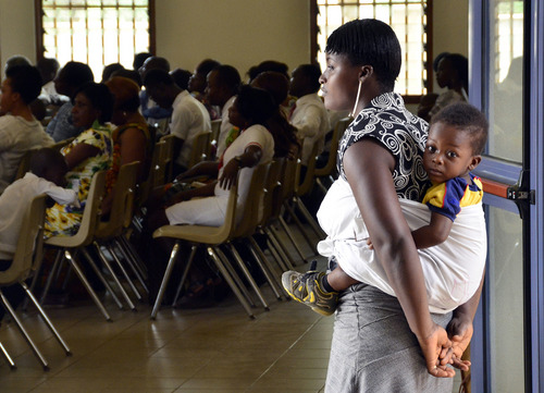 Mike Stack  |  special to The Salt Lake Tribune  LDS member Catherine Mensah calms her child outside LDS Sacrament meeting in Teishi, Ghana.  03/02/2014