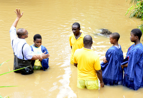 Mike Stack  |  special to The Salt Lake Tribune  Adventist Pastor Richard Daves baptizes a new convert in a overflowing river near Pokuase, Ghana.  03/01/2014