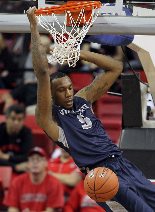 Utah State's Jarred Shaw dunks the ball during the first half of an NCAA college basketball game against San Diego State in the quarterfinals of the Mountain West Conference tournament Thursday, March 13, 2014, in Las Vegas. (AP Photo/Isaac Brekken)