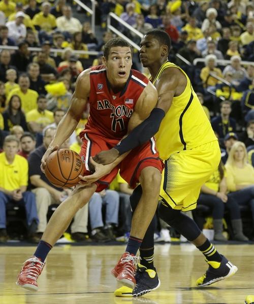 Arizona forward Aaron Gordon (11) is defended by Michigan forward Glenn Robinson III (1) during the second half of an NCAA college basketball game in Ann Arbor, Mich., Saturday, Dec. 14, 2013. (AP Photo/Carlos Osorio)