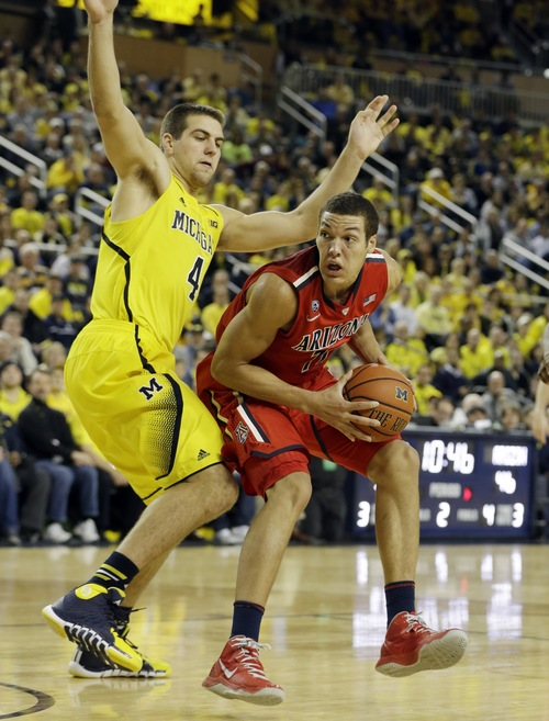 Arizona forward Aaron Gordon (11) is defended by Michigan forward Mitch McGary (4) during the second half of an NCAA college basketball game in Ann Arbor, Mich., Saturday, Dec. 14, 2013. (AP Photo/Carlos Osorio)
