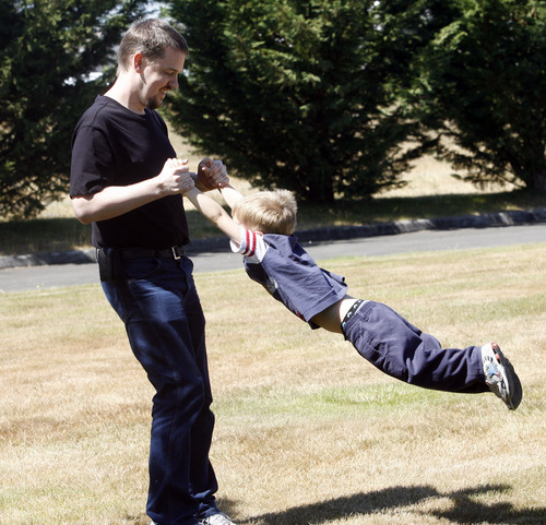 Rick Egan   |  Tribune file photo  Joshua Powell plays with his son Braden, in a park near his home, in Puyallup, Washington,  Friday, August 19, 2011