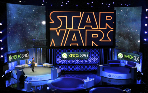 """FILE - In this June 14, 2010 file photo, Microsoft presents an upcoming LucasArts' """"Star Wars""""  video game for its new Xbox 360 with Kinect technology, during the 2010 Xbox 360 media briefing at the Wiltern Theater, in Los Angeles. With the launch of the Xbox One, PlayStation 4 and Wii U in the video game industry's rearview mirror, the spotlight at the Electronic Entertainment Expo, held June 10-12, 2014, is expected to shift back to games. From online-only titles to virtual reality experiences, about 200 exhibitors will  hype their latest software in hopes of driving away from E3 with The Next Big Thing. (AP Photo/Damian Dovarganes, file)"""