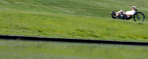 Steve Griffin  |  The Salt Lake Tribune   A recumbent bike rider pedals up a hill at Sugarhouse Park in  Salt Lake City, Utah Monday, June 9, 2014.
