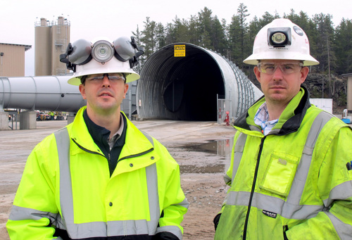 In this May 8, 2014 photo Eagle Mine advisors Dan Blondeau, left, and Andy Vaughn stand outside the mine's portal in Marquette, Mich. It's managers say the mine, a nickel and copper operation scheduled to begin production this fall, will pump $4 billion into Marquette County over its eight-year lifespan and employ about 300 while generating economic activity that will create 1,200 additional jobs. (AP Photo/John Flesher)