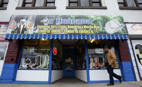 Helario Cazares, owner of the Monarca sporting goods store in Logan closes up shop for a moment to visit the store owner next door at La Huacana.  Since the raids on illigal immigrants at the local meat packing plant now called Miller, Cazares has seen a drastic drop in business.  With his clientele being primarily latino many people are just not spending the way they used to especially those that know they could be gone tomorrow.   Photo by Francisco Kjolseth/The Salt Lake Tribune 12/05/2007