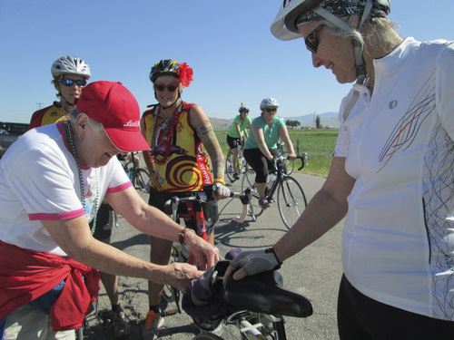 Kristen Moulton | Salt Lake Tribune  Alice Telford, left, adjusts some clothing hanging from Margy Batson's bike as Batson and her friends begin to ride in the Little Red Riding Hood all-women cycling event on Saturday, June 7, 2014, in Cache Valley. Telford, now 90, founded Little Red, and last rode three years ago.